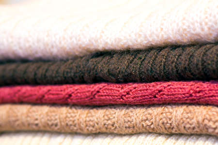 Stack of warm woolen cozy knitted sweaters Stock Photo