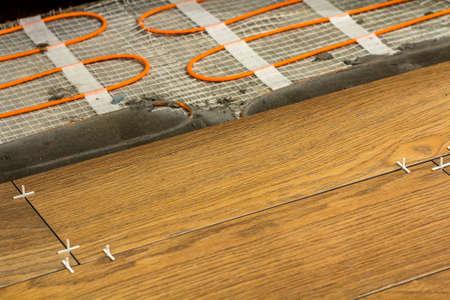 Instalação de telhas cerâmicas e elementos de aquecimento no piso de cerâmica quente. Conceito de renovação e melhoria. Foto de archivo - 93464551