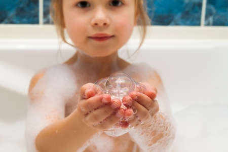 Childs little girls hands in bath with soap bubbles in it. Hygiene concept.