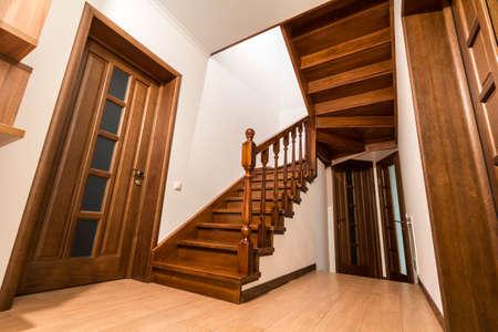 Escadas e portas de madeira modernas do carvalho marrom no interior renovado novo da casa