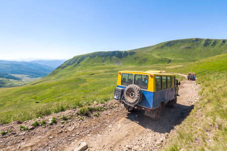 Off-road vehicle goes on the mountain gravel road way. Stock Photo