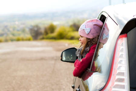Pretty little girl in the car looking through car window. Travel concept.