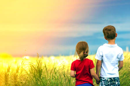 Little boy and little girl standing holding hands looking on horizont