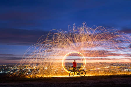 Firework showers of hot glowing sparks from spinning steel wool over night city background.