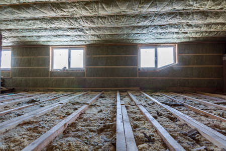 House attic under construction. Mansard walls and ceiling insulation with rock wool. Fiberglass insulation material in wooden frame for cold barrier. Stock Photo