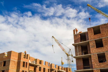 Baustelle eines neuen Wohnhochhauses mit Turmkranen gegen blauen Himmel. Wohngebietsentwicklung. Immobilienprojekt-Wachstumskonzept. Standard-Bild - 96083777