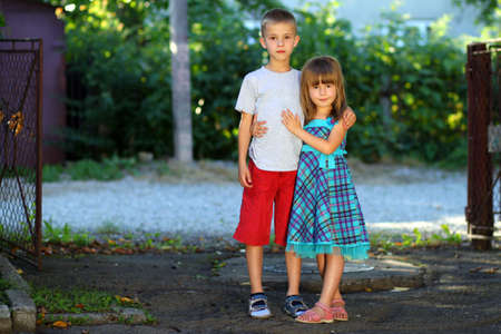 Two little children brother and sister together. Girl in dress hugging boy. Family relations concept. Archivio Fotografico