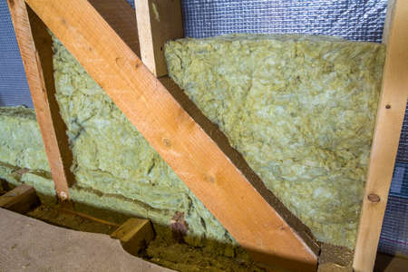 Thermal insulation mineral rock wool installation at the new building attic wall