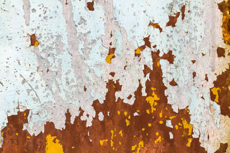 Abstract background texture of vertical grungy rusting metal plate with peeling paint and extensive corrosion with rust streaks. Reklamní fotografie