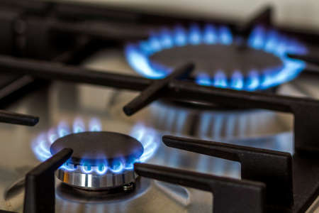 Natural gas burning on kitchen gas stove in the dark. Panel from steel with a gas ring burner on a black background, close-up shooting. Stock Photo
