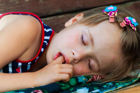 Portrait of sleeping pretty child girl who sucks her finger while sleeping. Children healthcare and well-being concept. Picture of peaceful adorable kid in bed having a nap. Sweet dreams. Good night.
