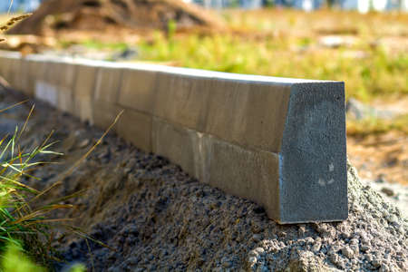 Concrete curb installation works at road construction site. Shallow DOF. Stock Photo