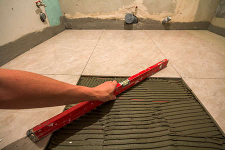 Ceramic tiles and tools for tiler. Worker hand installing floor tiles. Home improvement, renovation - ceramic tile floor adhesive, mortar, level. 스톡 콘텐츠
