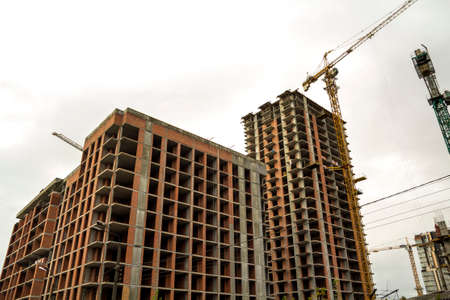 Ground view of a new modern residential house building under construction. Real estate development concept. Multi story home from bricks and concrete. Construction site tower crane at work. Banque d'images