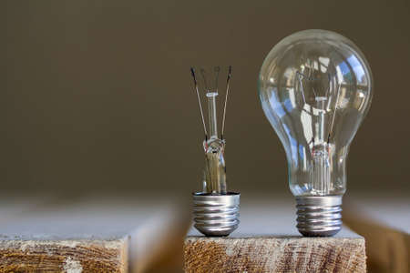 One broken and one whole electric light bulb on blurred background. Stockfoto