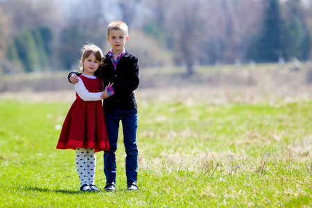 Portrait of beautiful children in new clothes standing together outdoors on bright blurred background, older brother embracing protectively sister. Happy friendship and family relations concept.