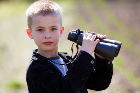 Portrait in profile of little handsome cute blond boy looking thoughtfully through binoculars in distance on blurred background. Children dreams, fantasies and imaginations concept. Stock Photo