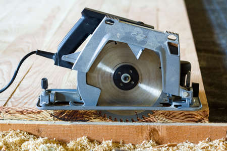 Close-up of new modern powerful circular electrical saw cutting wooden planks. Carpenters tool, construction, repairing and building concept.
