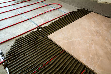 Ceramic tiles and tools for tiler. Floor tiles installation. Home improvement, renovation - ceramic tile floor adhesive,