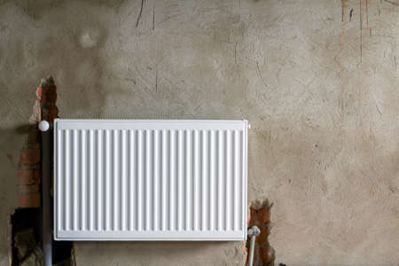 Close-up view of new isolated installed heating radiator on brick rough plastered wall in an empty room of a newly built apartment or house. Construction, maintenance, plumbing and repairing concept. Banque d'images - 100532117