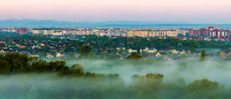 Beautiful panorama of morning aerial view of Ivano-Frankivsk city, Ukraine. Scene of quiet suburbs among green trees under dense fog and tall buildings on distant Carpathian mountains background. Stock fotó