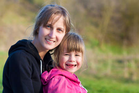 Portrait of young beautiful blond girl hugging lovingly and protectively her small preschool toothless sister, both smiling happily in camera outdoors. Happy family relations and friendship concept.