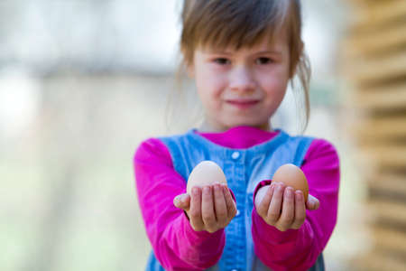 Blurred portrait of cute funny small smiling happy blond girl holding and showing proudly to camera two big clean hen eggs outdoors. Healthy food and children helping at chicken farming concept.
