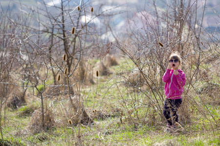 Portrait of cute small confused blond girl in casual pink clothing and dark sunglasses standing alone lost among dry prickly bushes and calling for help. Fears and dangers in children imagination. Stock Photo