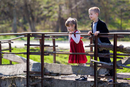 Two blond pretty children, small long-haired girl and cute boy leaning on wooden railings of old bridge looking intently down on warm sunny day. Children curiosity, dreams and fantasies concept. Stock Photo