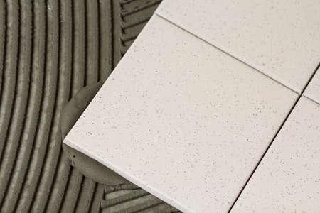 Ceramic tiles and tools for tiler. Floor tiles installation. Home improvement, renovation - ceramic tile floor adhesive
