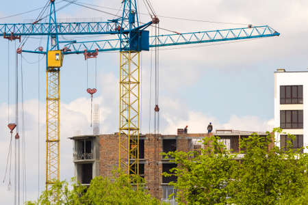 Urban view of silhouettes of two high industrial tower cranes working at construction of new brick building with workers in hard hats on it against bright blue sky and green top trees background. Stock fotó