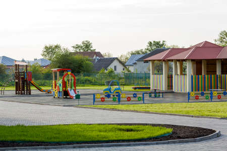 Bright new alcove with red tile roof and multicolored low fence on green lawn playground in kindergarten. Perfect place for happy games, recreation and entertainment, constructed with love and care.