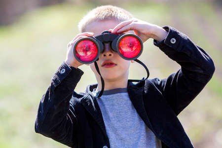 Portrait of little cute handsome cute blond boy watching intently something through binoculars in distance on blurred background. Children innocence, dreams, fantasies and imaginations concept. Stock Photo