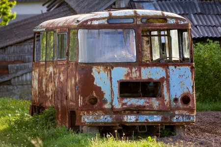 Close-up of old forsaken passenger bus with broken windows rusting in high green weedy grass on edge of plowed brown field on bright spring day under blue morning sky. Stock Photo