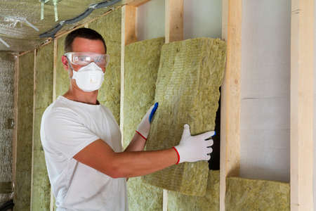 Worker in protective goggles and respirator insulating rock wool insulation in wooden frame for future house walls for cold barrier. Comfortable warm home, economy, construction and renovation concept Stockfoto