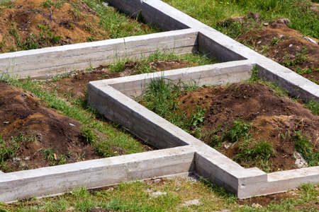Building site in green field. Close-up detail of trenches dug in ground and filled with cement as foundation for future house. Building, construction, investment and real property concept.