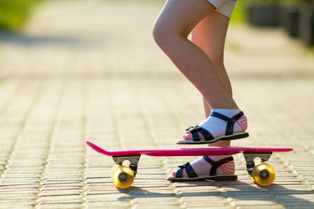 Child slim legs in white socks and black sandals on plastic pink skateboard on bright sunny summer blurred copy space pavement background. Outdoors activities and healthy lifestyle concept. 版權商用圖片