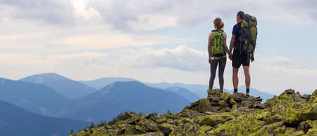 Back view of young tourist couple with backpacks, athletic man and slim girl stand holding hands on rocky mountain top enjoying mountain panorama. Tourism, traveling and healthy lifestyle concept.
