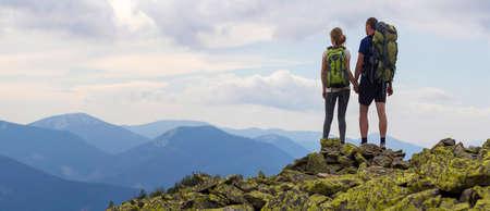 Achteraanzicht van jonge toeristische paar met rugzakken, atletische man en slank meisje staan hand in hand op rotsachtige bergtop genieten van bergpanorama. Toerisme, reizen en een gezonde levensstijl. Stockfoto