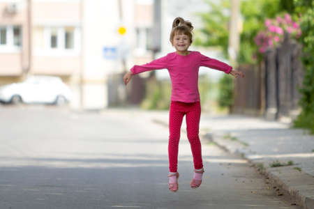 Cute small funny smiling toothless girl in pink casual clothing with long blond pony tail jumping and having fun on blurred bright sunny street outdoors background. Happy careless childhood concept.