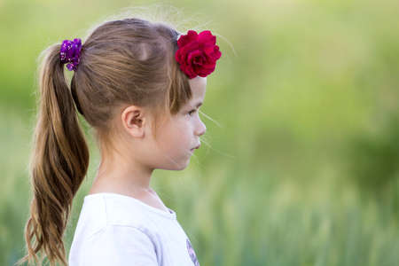 Profile portrait of cute small serious girl in white T-shirt with long blond pony-tail and red rose in hair on blurred bright green copy space background. Beauty of childhood concept.