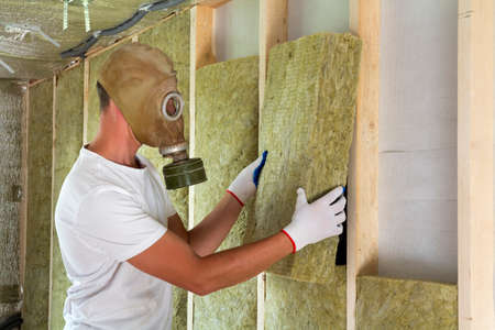 Young worker in gas mask insulating rock wool insulation staff in wooden frame for future house walls for cold and heat barrier. Comfortable warm home, economy, construction and renovation concept.