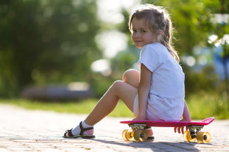 Pretty cute little blond girl in white shorts and T-shirt sitting on pink skateboard and smiling in camera on a light blurred summer background. Children activities and active lifestyle concept. Banque d'images