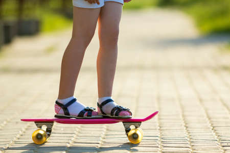 Girl slim legs in white socks and black sandals standing on pavement on plastic pink skateboard on bright sunny summer blurred background. Outdoors activities and healthy lifestyle concept.