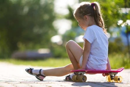 Profile portrait of pretty small long-haired blond girl in white clothing sitting on skateboard on bright summer day on blurred bokeh background. Children activities and active lifestyle concept.