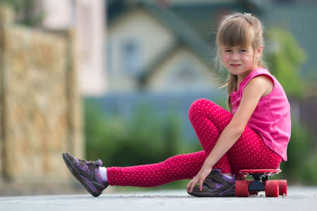 Pretty young long-haired blond child girl in casual pink clothing sitting on skateboard on paved suburb street on blurred sunny summer green background. Children activities, games and fun concept.
