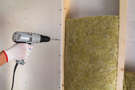 Close-up of worker hand with electric screwdriver fastening drywall to wooden timber frame with insulation mineral rock wool staff. Warm home, low energy bills, construction and renovation concept.