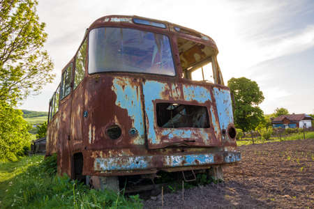 Close-up of old forsaken passenger bus with broken windows rusting in high green weedy grass on edge of plowed brown field on bright spring day under blue morning sky on small peasant huts background.