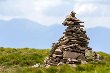 Lit by bright summer sun uneven mountain stones stacked and balanced like pyramid pile on green grassy valley on light white blue copy space sky background. Tourism. Traveling and landmark concept. Imagens