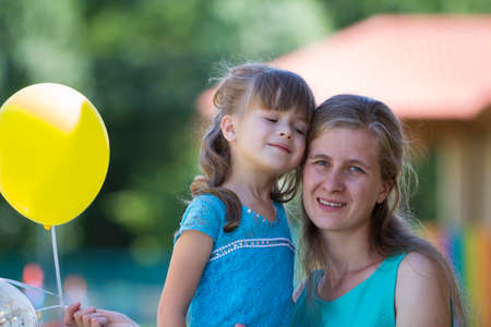 Young blond smiling happily mother hugs lovingly and protectively her small pretty preschool daughter girl with bright balloons on blurred bokeh background. Happy family relations and love concept.